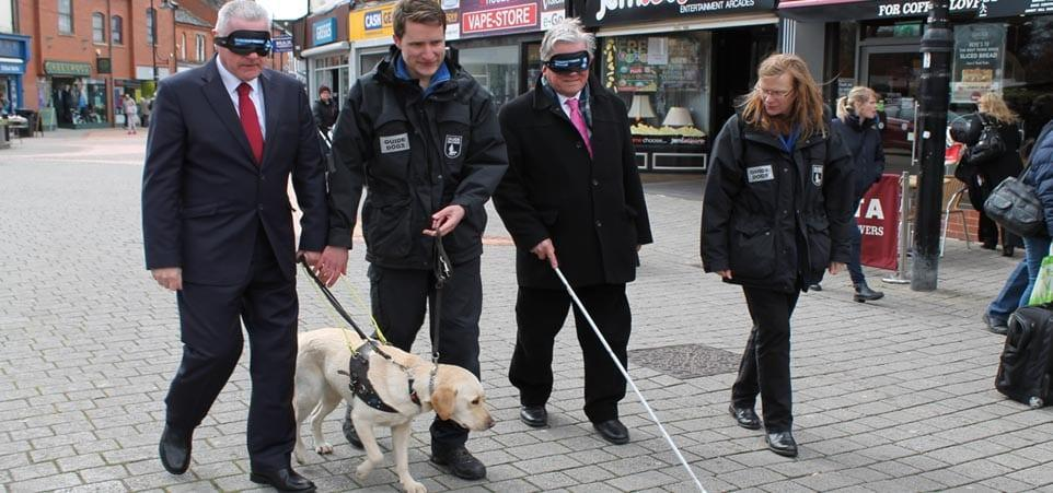 Gedling MP and council leader walk through Arnold town centre in blindfolds to support Guide Dogs cause
