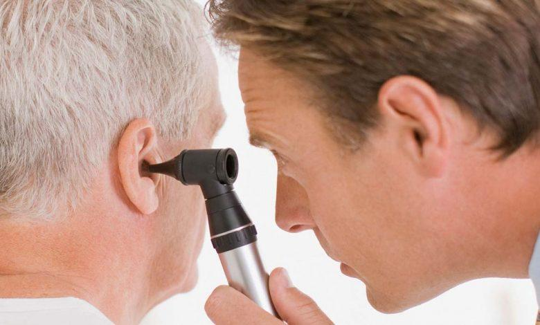 Man examines someone's ear