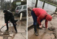 Photo of Councillors help clear thick mud that was trapping elderly people in their properties after flooding in Burton Joyce