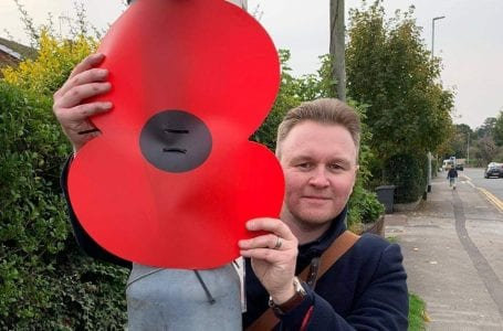 PICTURED: Cllr Payne with one of the giant poppies being placed around Redhill